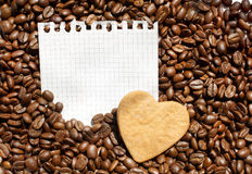 Coffee beans and heart on notepad sheet. Detached notepad graph paper sheet with heart shaped cookie on roasted coffee beans background Royalty Free Stock Photography