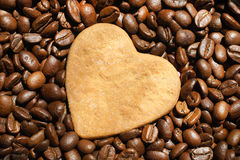 Coffee beans and heart. Roasted coffee beans with heart shaped cookie on a top Royalty Free Stock Photos