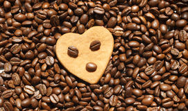 Coffee beans and heart. Roasted coffee beans with heart shaped cookie on a top Royalty Free Stock Images
