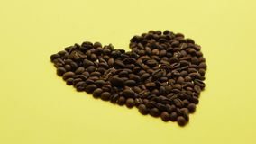 Coffee beans in heart shape. Composition of roasted brown coffee beans composed in shape of heart on surface of yellow color stock footage