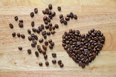 Coffee beans in heart shape on wooden panel Stock Photo