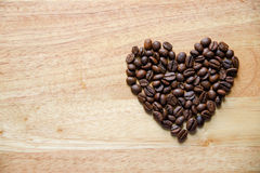 Coffee beans in heart shape on wooden panel Royalty Free Stock Photos