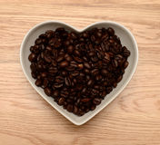 Coffee beans in heart shaped bowl Royalty Free Stock Image