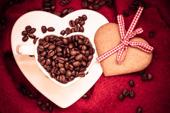 Coffee beans in heart shaped cup and dessert on red Royalty Free Stock Photo