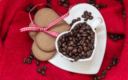 Coffee beans in heart shaped cup and dessert on red Royalty Free Stock Image