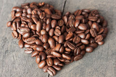 Coffee beans heart. Some coffee beans on a board like a heart Royalty Free Stock Photos