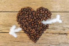 Coffee beans heart stabbed by white sugar Royalty Free Stock Photography