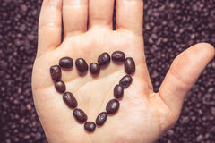 Coffee beans heart symbol on top of the hand Stock Photos