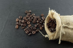 Coffee beans and hemp sack bag isolated on wood background Stock Images