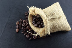 Coffee beans in hemp sack bag  on wood background Royalty Free Stock Images