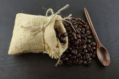 Coffee beans in hemp sack bag with wood spoon on wood Royalty Free Stock Images