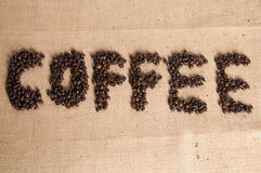 Coffee beans on hessian sack. Coffee spelled out in roasted beans Royalty Free Stock Image