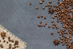 Coffee beans and ingredients on black stone background, top view stock photography