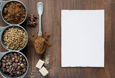 Different types of coffee and white card are on a wooden backgro. Coffee beans, instant coffee and ground coffee in a metal measuring cup as well as sugar cubes Stock Image