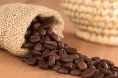 Coffee Beans in Jute Bag. Roasted coffee beans in jute bag on wood with woven basket in the back (Selective Focus, Focus on the coffee beans turned to the front Stock Photography