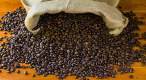 Coffee-beans in jute. On wood background Royalty Free Stock Photography