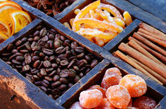 Coffee beans, kumquats and spices in wooden box. Coffee beans, kumquats, cinnamon, candied peels, sugared orange slices and star anise in rusted wooden box royalty free stock photography