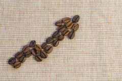 Coffee beans are laid out as a graph rising up on a beige napkin Royalty Free Stock Image