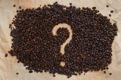 Coffee beans are laid out on old paper. A question mark is drawn royalty free stock image