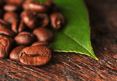 Coffee beans and leaf. On the wooden background Royalty Free Stock Photos
