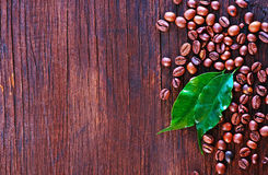 Coffee. Beans and leaf on the wooden table Royalty Free Stock Photos