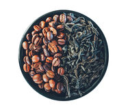 Coffee beans and leaves of black tea in a saucer isolated on white background. Top view closeup Royalty Free Stock Images