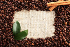 Coffee beans with leaves and cinnamon on a burlap sack Stock Images