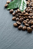 Coffee beans and leaves on dark background, space for your text Stock Photos