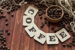 Coffee beans and letters. Coffee with cinnamon on the table with the inscription Royalty Free Stock Photography