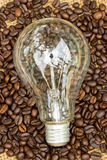 Coffee beans and light bulbs on vintage linen Stock Photos