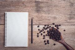 Coffee beans and and lined paper on wooden table top view. Close up coffee beans and and lined paper on wooden table top view Stock Image