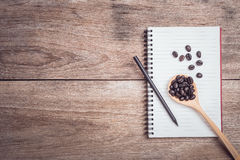 Coffee beans and and lined paper on wooden table top view. Close up coffee beans and and lined paper on wooden table top view Stock Photography