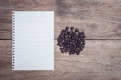 Coffee beans and and lined paper on wooden table top view. Close up coffee beans and and lined paper on wooden table top view Stock Photo