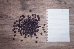 Coffee beans and and lined paper on wooden table top view. Close up coffee beans and and lined paper on wooden table top view Royalty Free Stock Images