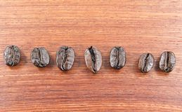 Coffee beans lined up on a wooden floor Stock Image