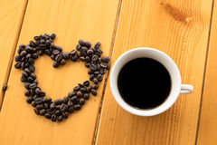 Coffee beans Love cup on wood table Stock Photos