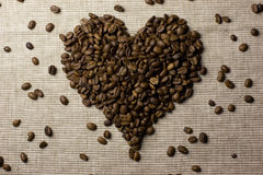 Coffee beans love heart. Dark brown coffee beans in shape of love heart with hessian background Stock Image