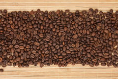 Coffee beans lying on a bamboo mat Royalty Free Stock Images