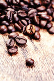 Coffee beans on macro ground coffee background, top view image. Stock Photos