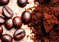 Coffee beans on macro ground coffee background, top view image. Royalty Free Stock Photos