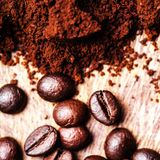 Coffee beans on macro ground coffee background, top view image. Royalty Free Stock Photography