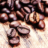 Coffee beans on macro ground coffee background, top view image. Stock Image