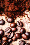 Coffee beans on macro ground coffee background, top view image. Royalty Free Stock Image