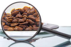 Coffee beans and magnifier Royalty Free Stock Images
