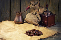 Coffee beans, manual coffee grinder and coffee maker on sacking Royalty Free Stock Photo