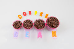 Coffee beans in measuring cups of various sizes on white Stock Photos