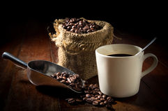 Coffee beans in metal scoop and with cup and gunny sack. Stock Image