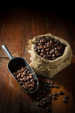 Coffee beans in metal scoop and gunny sack. Stock Photos