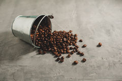 Coffee beans in a metal small bucket scattered on the gray concr Royalty Free Stock Photo