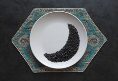 Coffee beans in moon shape on a plate. Ramadan concept stock photography